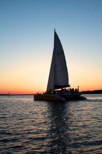 orange beach al sail at sunset on a 53' Catamaran Sailboat