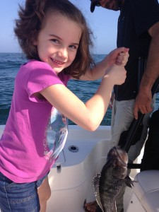 young TN angler with a big smile with her sea bass along the AL gulf coast
