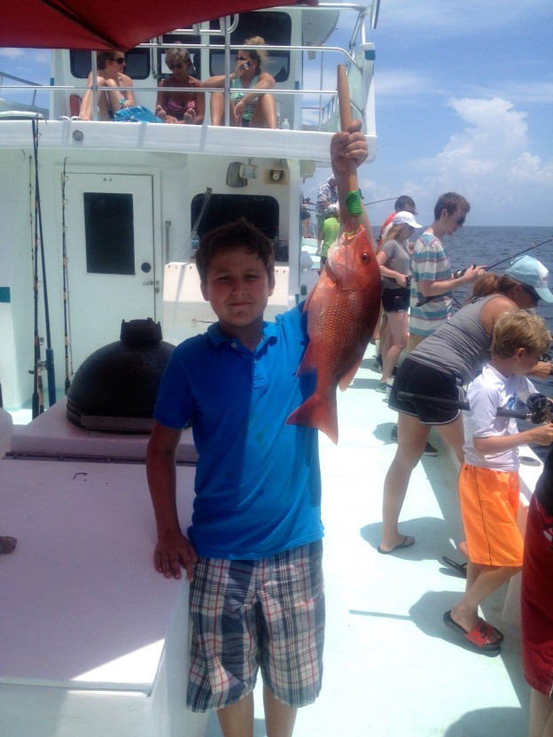 party boat fishing gulf shores al happy tx boy with his red snapper on the back deck of the AL party boat Miss E