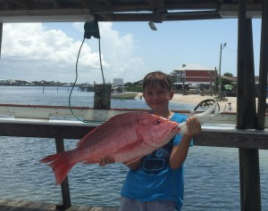 party boat fishing on the AL Gulf Coast on the Miss E happy boy with his red snapper
